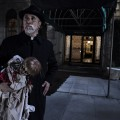 Tony Amendola (Father Perez) with the Annabelle doll in New Line Cinema's supernatural thriller, Annabelle. Photo: Warner Brothers