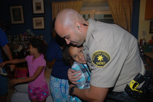A Sheriff's deputy hugs a child during Operation Secret Santas. Courtesy photo.