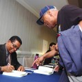 Jazz legend Herbie Hancock signs a copy of his book for Bobby Watson, director of Jazz Studies at University of Missouri-Kansas City. Photo: Gina Yarbrough/San Diego County News