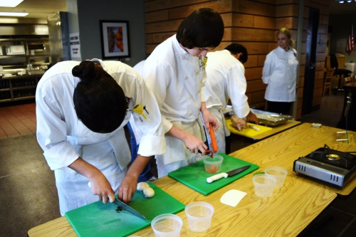 From left, Vista High student Orion Araujo and Justin Marek practice preparing a meal while Chef Instructor Kim Plungett  looks on. Photo: Gina Yarbrough/San Diego County News
